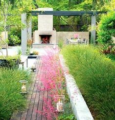 Low cement wall, great decking, fireplace, greenery, and bright pink flowers- love it all