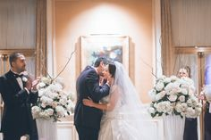 Bride and groom kiss during their wedding ceremony at the Essex House in NYC. Captured by NYC wedding photographer Ben Lau.