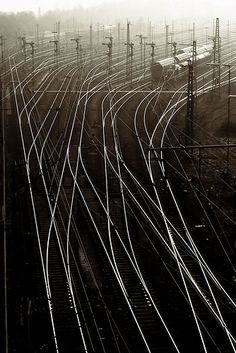 Composition of an array of tracks running from dark to light and the mist above them.