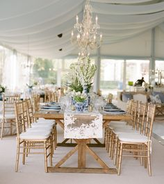 Wedding reception design with uncovered wooden tables, lace runners, white florals in blue and white chinoiserie vases and place settings of blue and white china and cut crystal stemware. Event design and florals by Lauren Chitwood Events, image by Bella Grace Studios.