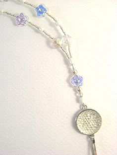 #Handmade #jewelry on #Zibbet! You'll fall in love with this #IDbadge floral #lanyard with its sparkling clear glass beads with an aurora borealis finish.  It features a focal bead of faceted clear glass in a honeycomb arrangement of tiny facets in a flattened dome, set in a silvertone round frame. Clear flower beads and round faceted beads, both with a partial aurora borealis finish, add to the sparkle.