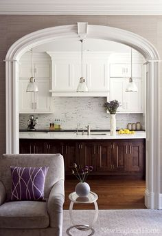 A graceful archway connects the kitchen and family room, allowing the two rooms to flow as one. Two Tone Kitchen Cabinet Ideas To Avoid Boredom in Your Home Kitchen Inspirations, Kitchen Cabinet Design, Kitchen Style, Wooden Kitchen Cabinets, House And Home Magazine, New Kitchen Cabinets, Modern Walnut Kitchen, Kitchen Renovation, Walnut Kitchen Cabinets