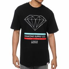 """The Diamond Supply 15 Years Brilliance black tee shirt for guys is here to amp up your summer wardrobe. Coming in a crisp black colorway this standard fit crew neck tee shirt features short sleeves, a durable and comfortable cotton construction and a custom logo tag at the bottom front hem. Printed at the front of this crew neck tee there is a white diamond graphic with red and mint stripes along with """"Diamond Supply Co."""" and """"15 Years Of Brilliance"""" printed below the graphic. Get your shine…"""