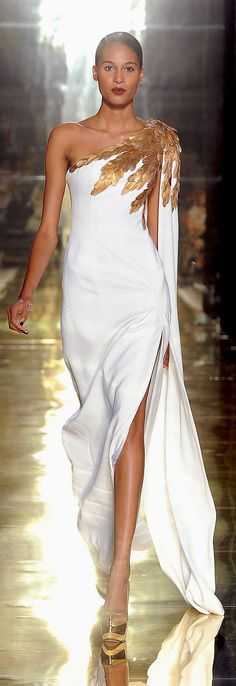 White one sleeve gown with gold feather detail on the shoulder created by Georges Chakra