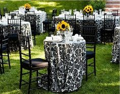 Damask wedding tablecloth decorations:  The accent of sunflowers are the perfect touch of color for the centerpieces!  Genius!