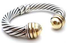 "High End Designer Jewelry Bracelets - This is a sterling silver hinged classic cable cuff bracelet with 14K gold domes by David Yurman. It measures 10mm wide, has an inside circumference of 6"" and an"
