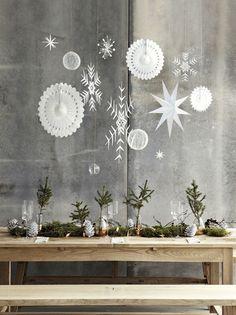 Mesa de Navidad en gris y verde, con el musgo y las ramas de pino como protagonista, y los colgantes de papel blanco como contraste.