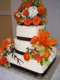 Wedding cake with lace and ribbon detail. Includes orange and fall colored accents. #weddingcake