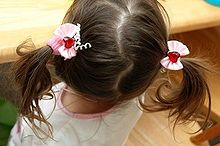 "Bunches (also called twintails, angel wings, two ponytails, dog ears, or pigtails) are a hairstyle in which the hair is parted down the middle and gathered into two symmetrical bundles, like ponytails, secured near the scalp. In some English-speaking regions, this hairstyle is referred to as ""pigtails,"" but in others, the term ""pigtails"" applies only if the hair is braided.[1] The style is often given to toddlers and young girls, and is sometimes also worn by teenagers and young women."