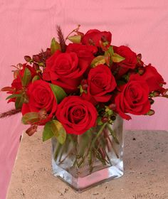 """"""" A Heavy Glass Vase of South American Roses  An elegant display of roses in the color of your choice, tastefully arranged with complimenting filler flowers and / or green foliage, in a heavy glass rectangular vase."""
