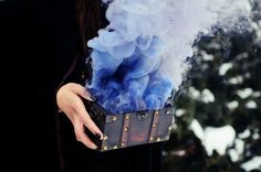 Imagine being at a funeral when a cloaked woman appears out of the shadows. She carries what looks like a treasure chest. In the middle of the service, she opens the chest, revealing a bright blue smoke. Write about what happens afterwards. Who is this woman and why is she doing this?