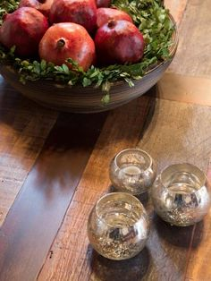 A bowl of red pomegranates and bright silver candle holders add a pop of color and light to the dark wood coffee table in the living room, as seen on HGTV's Fixer Upper.  (detail)