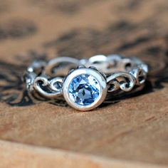 This unique silver swirl engagement ring features a 5mm bezel set Swiss blue topaz gemstone. This ring is inspired by waves of water and cast into recycled sterling silver. The blue topaz is set into a hand carved bezel, oxidized it to bring out the details and gave it a high polish. This ring is beautiful and unique and made with lots of love. Click here for the matching band: http://etsy.me/247IOa9 $240