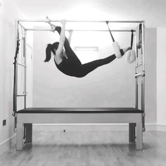 Challenge upper body strength and stretch hamstrings using the overhead crossbar with hanging scissorlegs. Keep quads engaged to maximise hamstring length during splits #Pilates #pilatescadillac ❤️