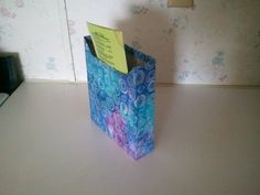 Front of cereal box covered with fabric & magnets attached to hang on the fridge.