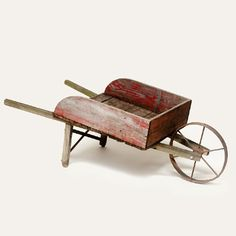 Rustic wooden cart with metal wheel and red chippy paint.