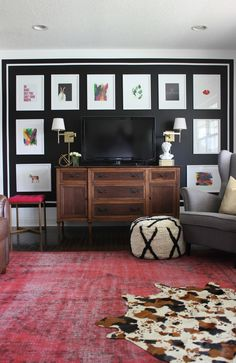 She painted an accent wall mostly black, framed it with white and then added gorgeous art - the TV practically disappears!
