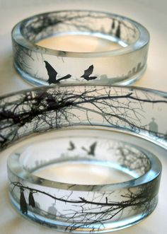 Clear resin bangles and rings with intricate tree branch and bat silhouettes by Keri Newton
