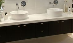 HOUSE ATLANTIC BEACH BY JOOS  Dark and light combine in this Atlantic Beach bathroom featuring stained mahogany floating units offset with a white Caesarstone top. The large freestanding bath is raised on a wooden platform – the perfect setting for romantic tête-à-têtes. http://joos.co.za/house-atlantic-beach-3/
