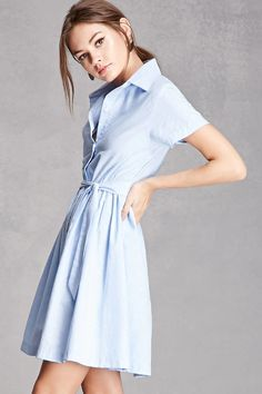 A swing dress by Compania Fantastica™ featuring a basic collar, button front, pleated skirt, and short sleeves.