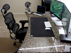 "Gorgeous granite desk setup with a Mac Mini driving dual Thunderbolt 27"" Displays and a MacBook Pro Retina"