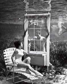From the 30's Bruce Mozart underwater image of man looking through window at woman underwater