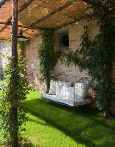 Coin sieste dans le jardin via une banquette romantique en fer forgé