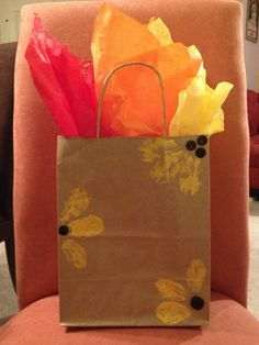How to Decorate a Gift Bag for Fall. Just use leaves as stamps, buttons, and fun fall tissue paper.