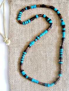 Excellent beaded necklace is designed with wood robles, Phillipine turquoise, and pen shell strung on elastic cord. No clasps makes this an easy to fit, easy to wear necklace for men. Phillipine turqu