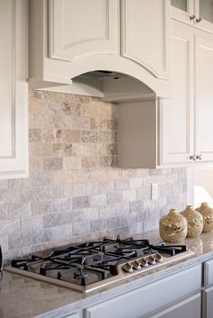 """A full wall, subway patterned silver travertine backsplash is surrounded by custom built cabinets in Sherwin Williams Shoji White. The 36"""" Kenmore gas cooktop completes the beautiful, yet functional look."""