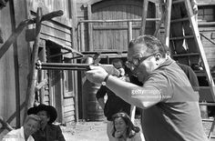 The director Sergio Leone shooting with a rifle on the set of the film The Good, the Bad and the Ugly. 1966