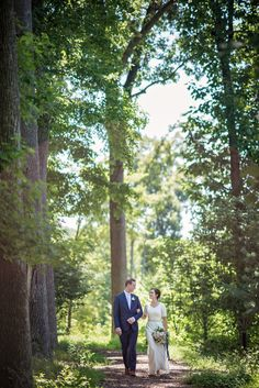 Bride and groom taking a stroll in the forest on their big day at summer barn wedding in Maryland
