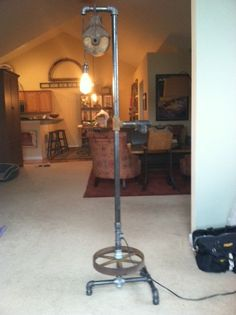 Floor lamp consisting of old and new iron pipe, vintage pulley and wheel