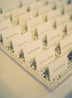 Escort cards sitting in pearls - loose pearl vase filler - available at www.yourweddingcompany.com