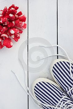 Sneakers and sea coral on a white wooden background. Vintage. Travel theme.