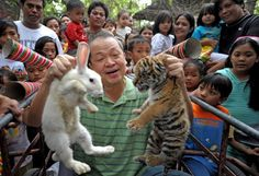 Zoo owner Manny Tangco (C) holds up a rabbit and a tiger cub while surrounded by local children at the Malabon Zoo in Malabon, in northern Metro Manila to illustrate the shift from the 'Year of the Tiger' to the 'Year of the Rabbit'. China and many other parts of Asia will celebrate the start of the 'Year of the Rabbit' at Lunar New Year in early February 2011, in accordance with the Chinese calendar that works on a 12-year cycle.