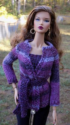 This is a cardigan and top sweater set for a 16 inch Integrity Toys fashion doll. The cardigan and top are knit top down in one piece, and the cardigan is closed with a belt.