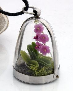 Orchid terrarium dome pendant- Wild woodland locket with realistic purple miniature polymer clay orchid, pebble and reindeer moss. $42.00, via Etsy.