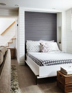 This Murphy bed uses a suspension system that makes it possible to lift with one finger. On both sides of the queen-size bed, a niche in the wall acts as a side table and is wired with a reading light.