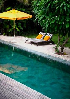 couple of lounge chairs next to a pool looks inviting