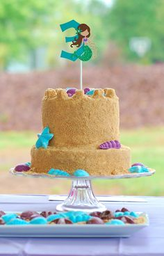 "Sandcastle birthday cake. Mermaid cake topper. White chocolate seashells. A two tiered yellow cake with chocolate filling, frosted in buttercream and covered in ""sand"". #mermaid #birthday #cake #sandcastle #kids #ocean #beach #girl #seashells"
