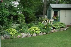 Shade area with hosta's lilies and rock border