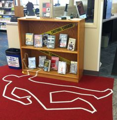 "Mystery Fiction Library Display Sherlock holmes silhouette, ""bleeding"" book, caution tape, murder victim outline Unique, creative, and abstract library display."