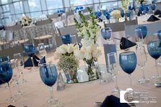 Mesas: toalhas brancas, taças azuis