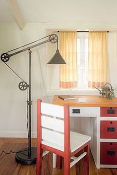 This work corner features a pulley floor lamp with rustic iron finish, a copper watering pot on the desk, and wrought-iron drawer handles.