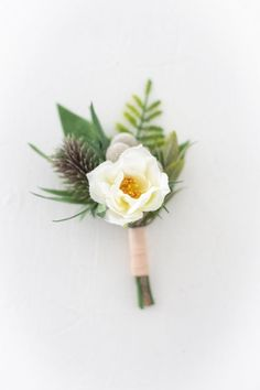 Faux Flower Boutonnière. Made with dried silver brunia, a thistle, a delicate cream wildflower, and greenery. How dapper would a groom look on his wedding day in this?! #weddingflowers #groom #groomstyle