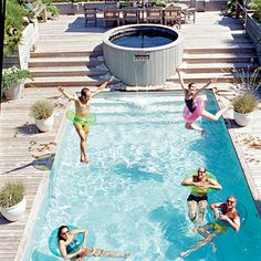 Family fun centers around this rectangular pool complete with a built in deck at the top and a hot tub.