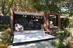 Fully decked out pop-up cafe made out of a converted shipping container and fitted with a hydraulic door and window. Designed by Ian Barker Gardens.