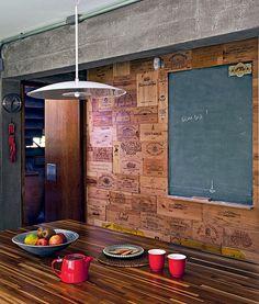 Ampliado com a área da antiga copa, a cozinha ganhou a ilha central com bancada de teca. A parede foi revestida com caixas de vinho desmontadas e uma lousa, para escrever o cardápio do dia. Projeto da arquiteta Flavia Petrossi