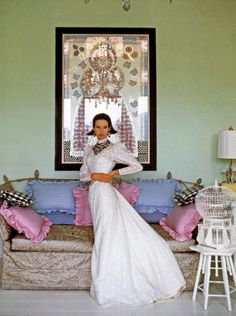 Gloria Vanderbilt posing in front of one of her collages, Gingham Queen Elizabeth, on the balcony at Summertime, her house in Southampton, photographed by Francesco Scavullo, New York, c. 1969.